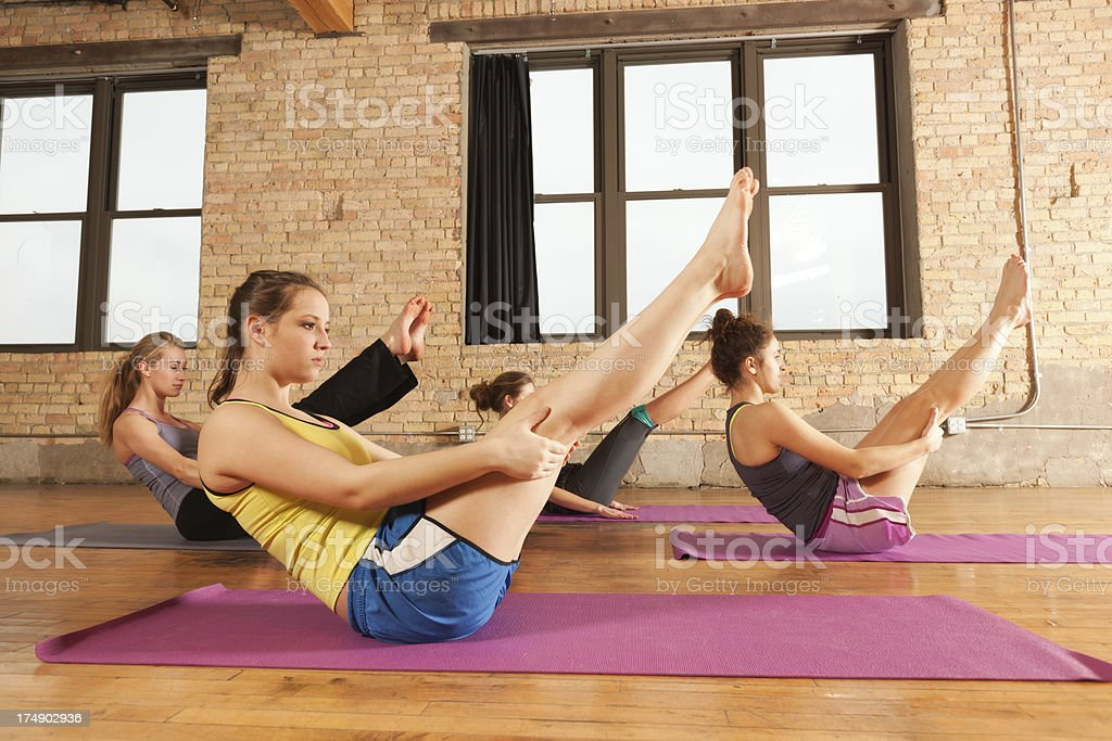 Young Women in Full Boat Pose Attending  Group Yoga Session royalty-free stock photo
