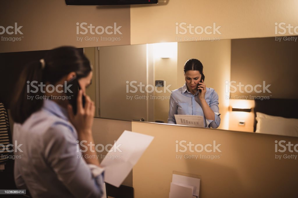 Business travel. Young women working in hotel room, checking paper...