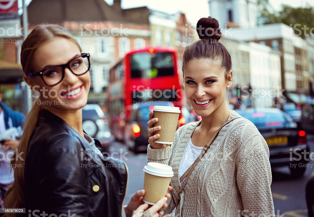 Young women in London Two young women standing on the city street, holding take coffee in hands and smiling at the camera. 20-24 Years Stock Photo