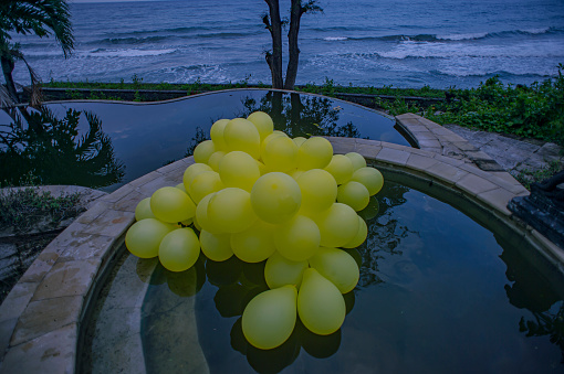 young women with yellow balloons at Bali island coast