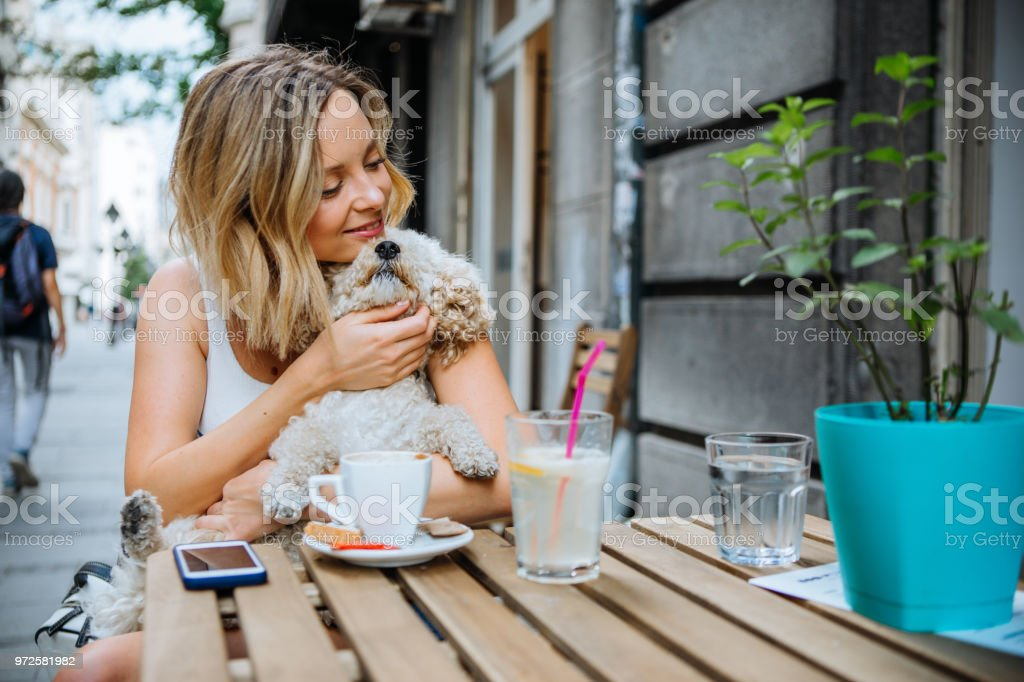 Young women with her dog, enjoy in weekend relaxation in cafe bar.