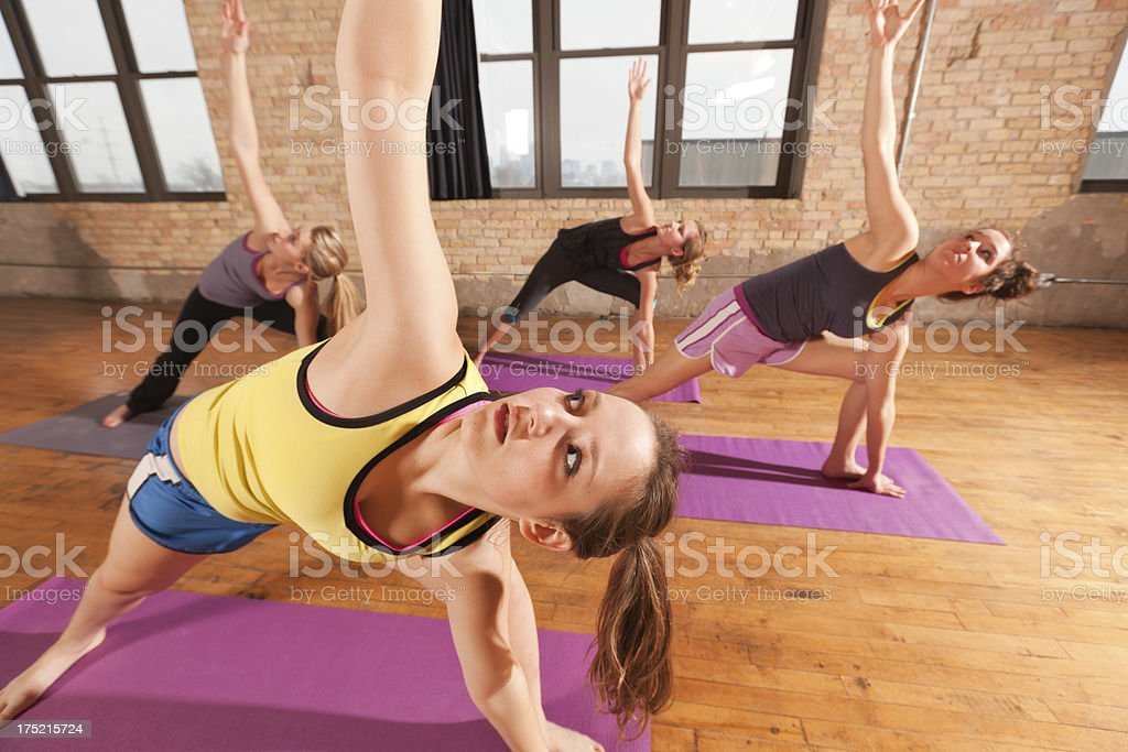 Young Women in Side Angle Pose Attending  Group Yoga Class royalty-free stock photo