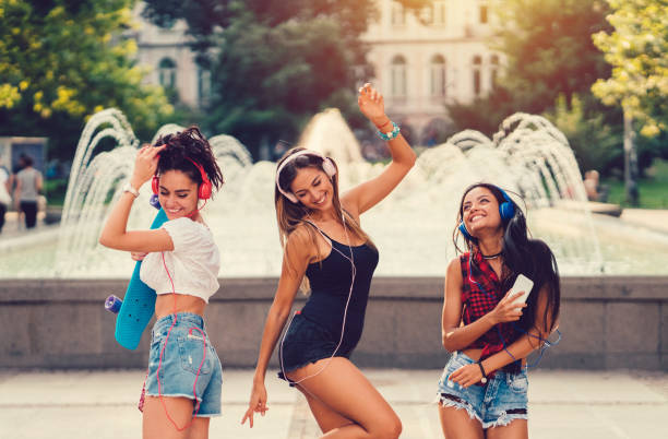 Young women in the city dancing on the music stock photo