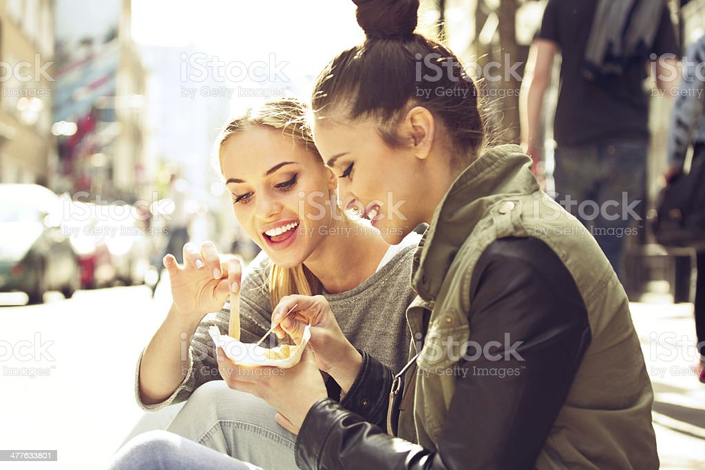 Young women in the city Two young women sitting on the city street and eating take away chips. 20-24 Years Stock Photo