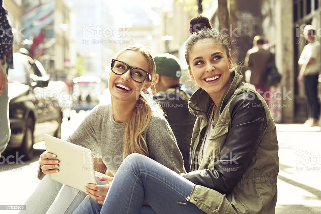 Young women in the city Two smiling young women sitting on the city street, one of them holding a digital tablet. 20-24 Years Stock Photo