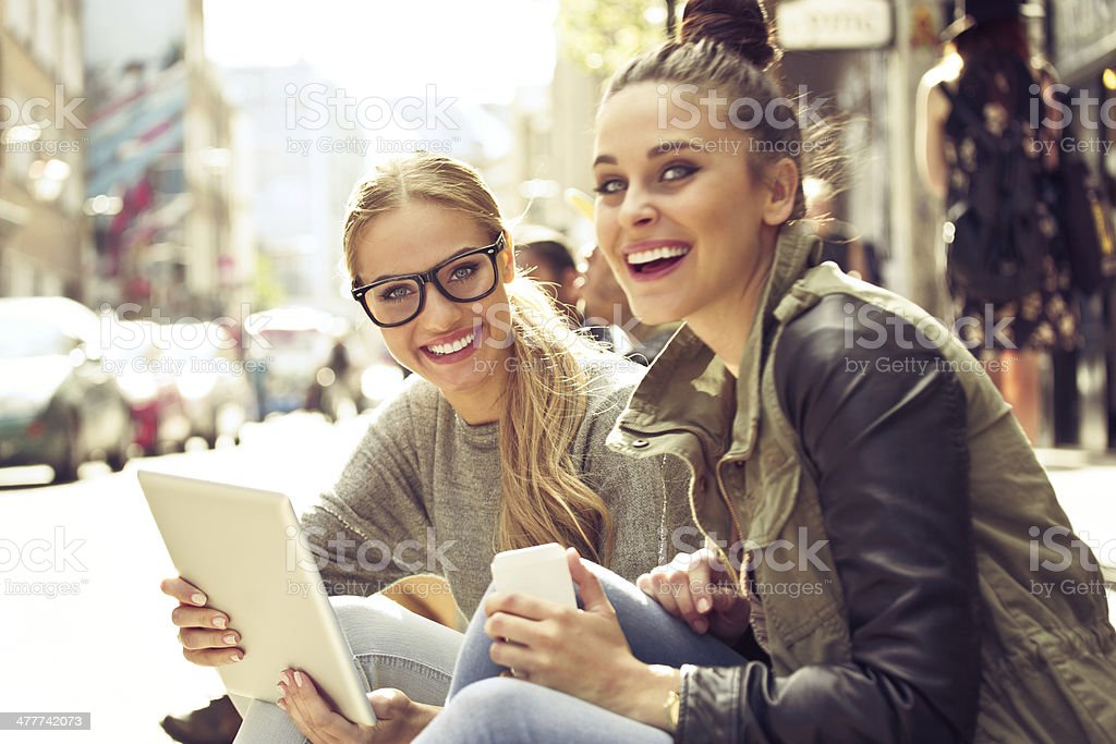 Young women in the city Two young women sitting on the city street, holding a digital tablet and smart phone in hands and smiling at camera. 20-24 Years Stock Photo