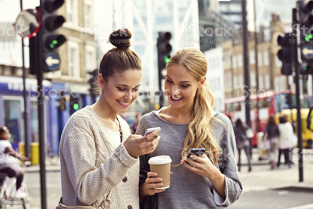Young women in the city Smiling two young women standing on the street and using smart phone.  20-24 Years Stock Photo