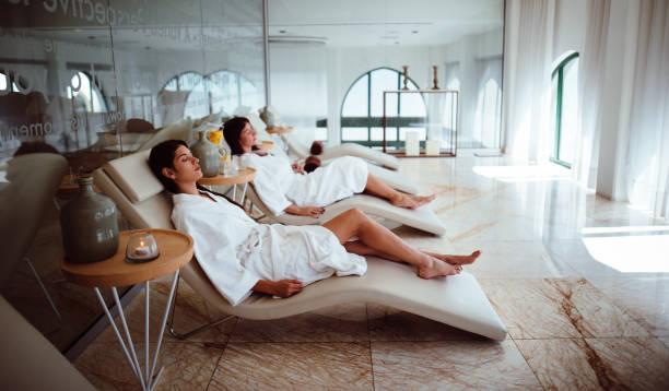 młode kobiety w białych szatach relaks w centrum kosmetycznym - kurort turystyczny zdjęcia i obrazy z banku zdjęć