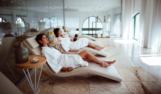 young women in white robes relaxing at beauty spa centre - spa foto e immagini stock