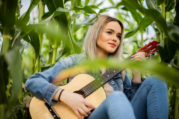 Young women is sitting at field and playing guitar