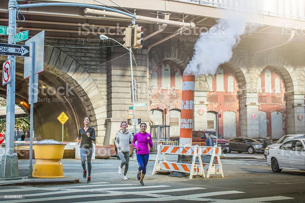 Young women jogging by smoke stack on road stock photo