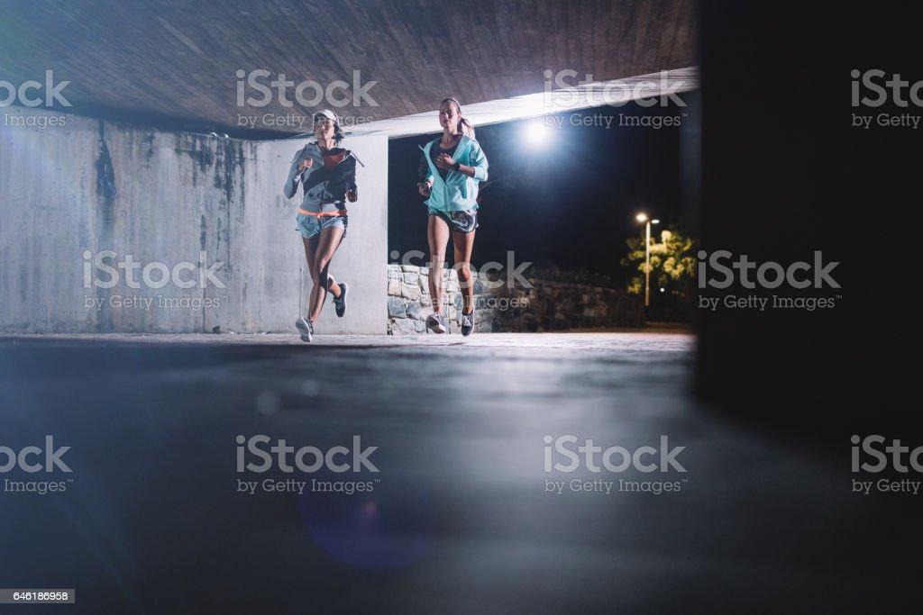 Young women jogging under bridge at night stock photo