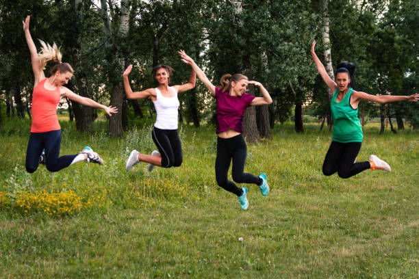 Young women jumping in field stock photo