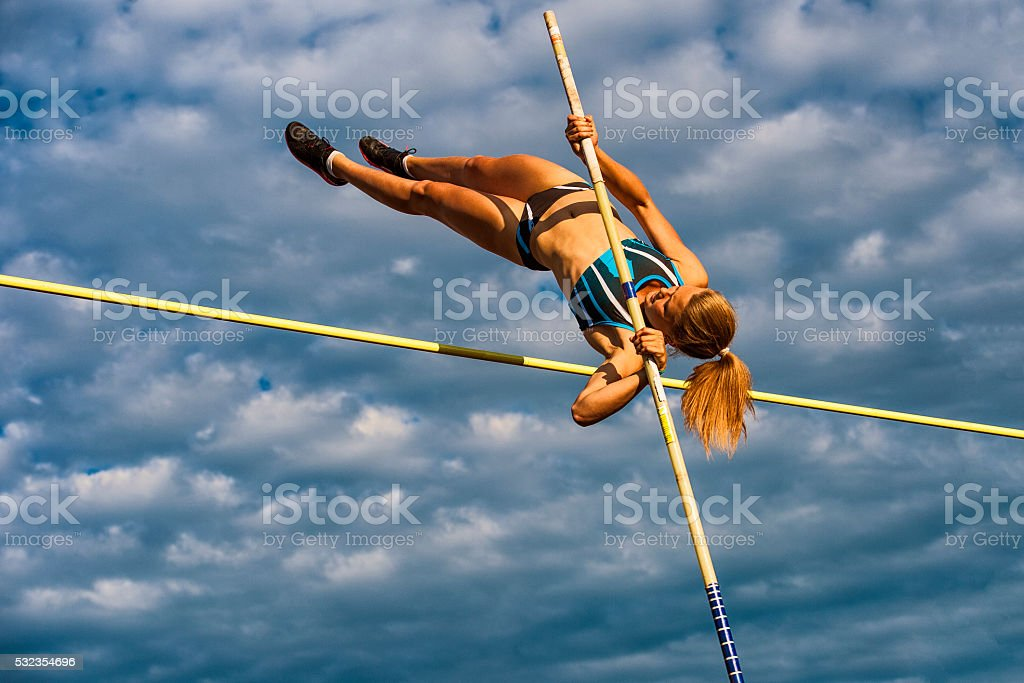 Young Women Jumping Over the Lath Against Cloudy Sky stock photo