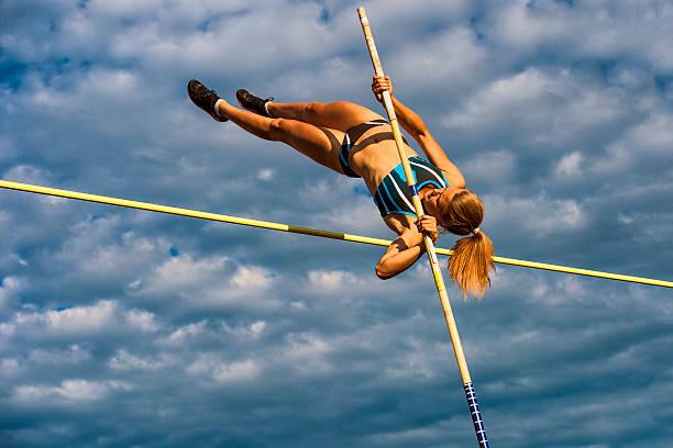 Junge Frauen springen über die Lath gegen bewölkten Himmel – Foto