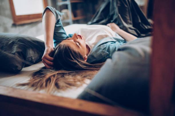 jonge vrouwen tot op bed - buikpijn stockfoto's en -beelden