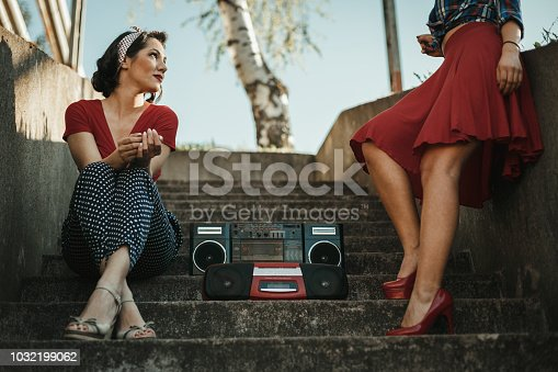 istock Young women listening to music from a boom box and having fun outdoors 1032199062