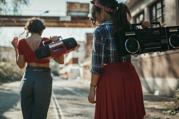 Young women listening to music from a boom box and having fun outdoors stock photo
