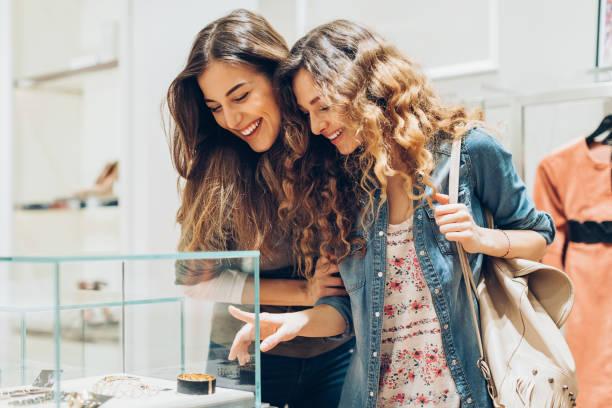 junge frauen betrachten goldschmuck in der mall - diamanten kaufen stock-fotos und bilder