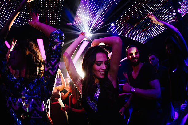 Young women loves dancing with friends in the club Young women dancing happily with her friends in a nigh club party with disco lights nightclub stock pictures, royalty-free photos & images