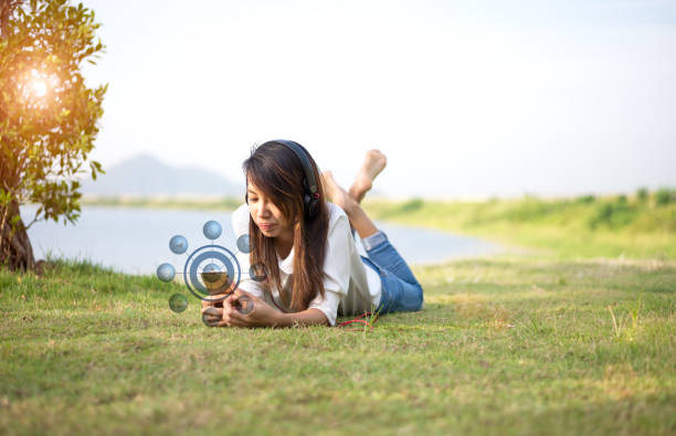 unga kvinnor ligger i sommar gräs med hörlurar lyssna på musik, avkoppling och shopping online, solig dag, - happy indie pop bildbanksfoton och bilder