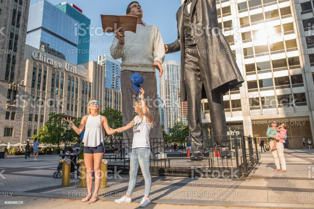 Young women making a funny pose in front of the famous Lincoln statue in Chicago stock photo
