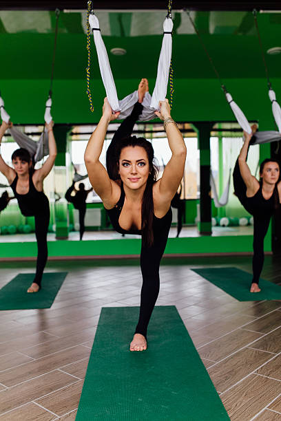 young women making antigravity yoga exercises with a group of stock photo