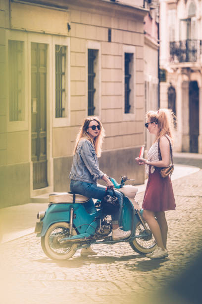 young women meeting on city street and talking - giovani motorino italia parlano foto e immagini stock