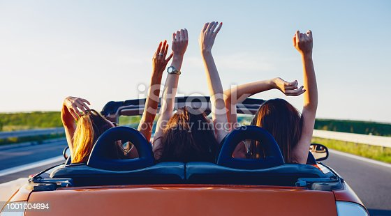 Young women on a road trip with cabriolet