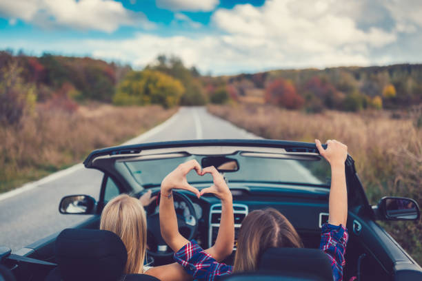 Young women on a road trip with cabriolet stock photo