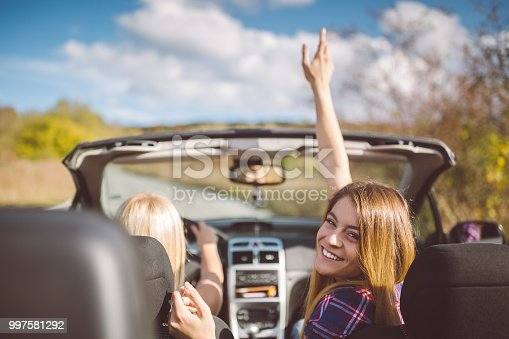 1131372580 istock photo Young women on a road trip with cabriolet 997581292