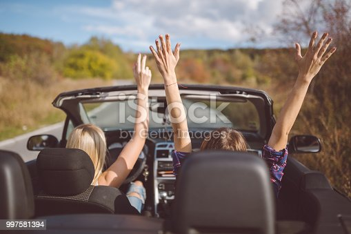 1131372580 istock photo Young women on a road trip with cabriolet 997581394