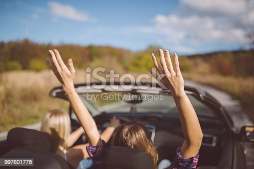 1131372580 istock photo Young women on a road trip with cabriolet 997601778