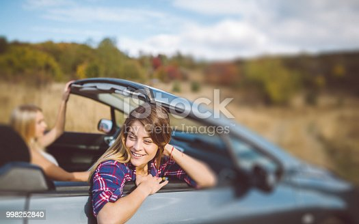 1131372580 istock photo Young women on a road trip with cabriolet 998252840