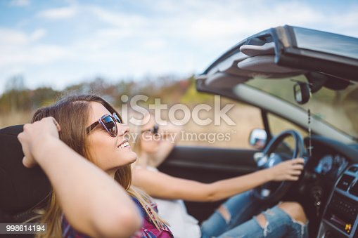 1131372580 istock photo Young women on a road trip with cabriolet 998614194
