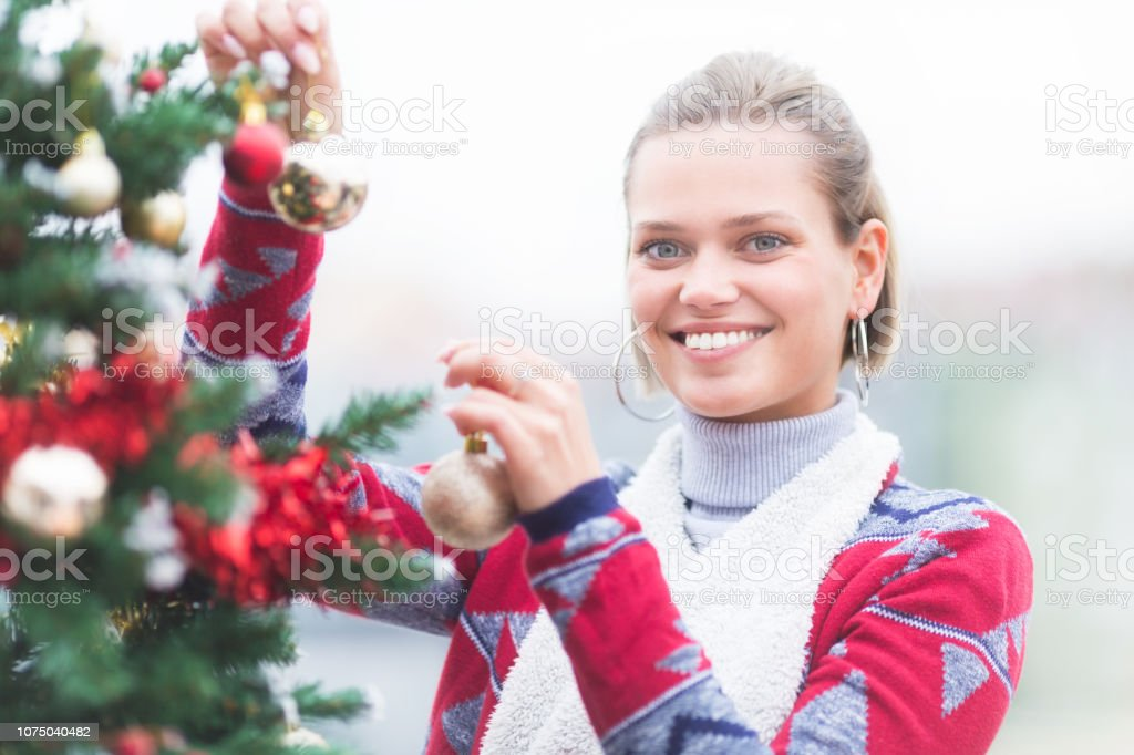 Young women on balcony decorating Christmas tree and smiling stock photo