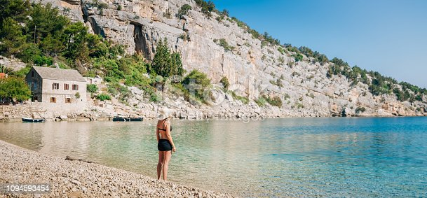 Beautiful landscape of beach in Dubrovnik,Croatia with young woman in bikini watching the horizon.