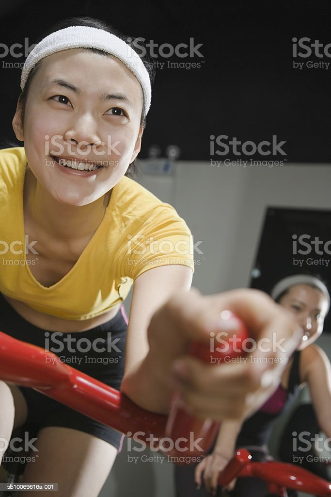 Young women on exercise bikes in gym, smiling (focus on foreground) foto de stock libre de derechos