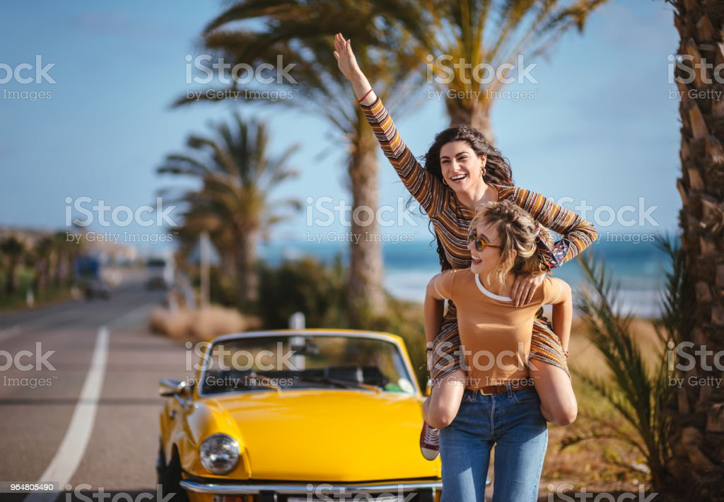 Young women on road trip having fun with piggyback ride royalty-free stock photo