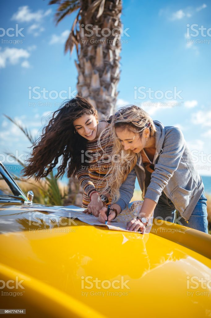 Young women on road trip reading map for route planning royalty-free stock photo
