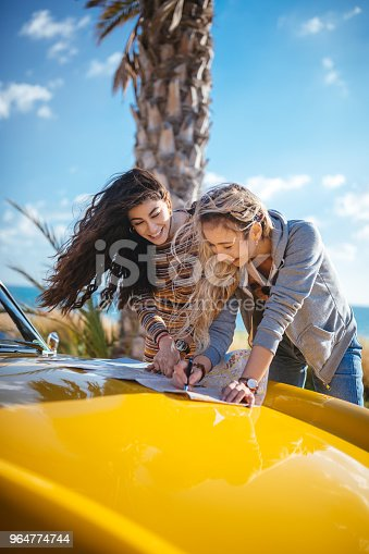 Young Women On Road Trip Reading Map For Route Planning Stock Photo & More Pictures of 20-29 Years