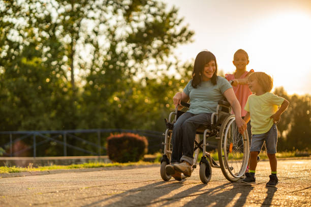 Young women on wheelchair walking with kids at sunset Disability women enjoying with kids in nature paralysis stock pictures, royalty-free photos & images