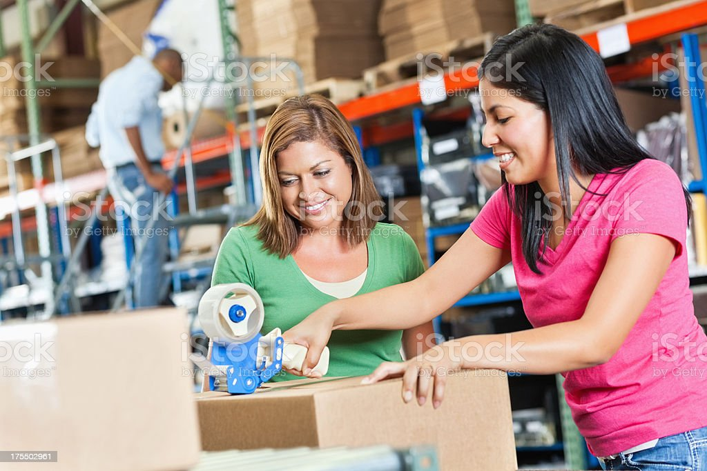 Young women packing boxes in warehouse distribution center stock photo