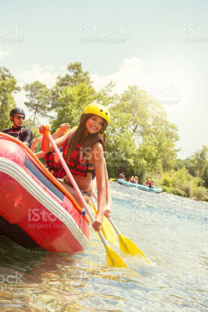 Young women paddling in whitewater raft stock photo