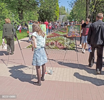 Voronezh, Russia - May 9, 2015: Young women paint on the canvas in the easel on the city public garden during the Victory Day celebration by townsfolk on the city central square