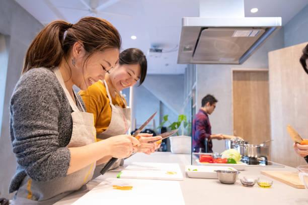 料理教室で野菜を剥離の若い女性 - 教室 ストックフォトと画像