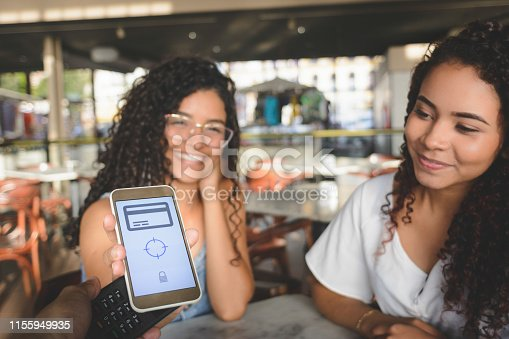 Young women placing a smartphone on a credit card machine for contactless digital payment. Focus on device screen.
