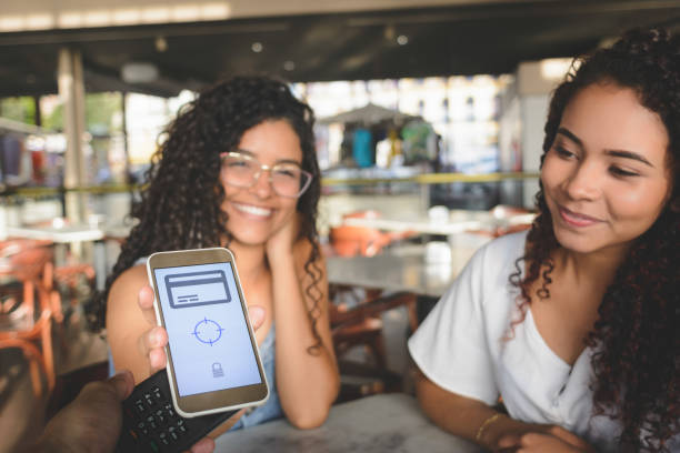 Young women placing a smartphone on a credit card machine for contactless digital payment stock photo