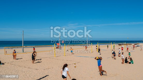 Cascais, Portugal - June 10, 2019: Young women play volleyball on the beach in Carcavelos, Portugal