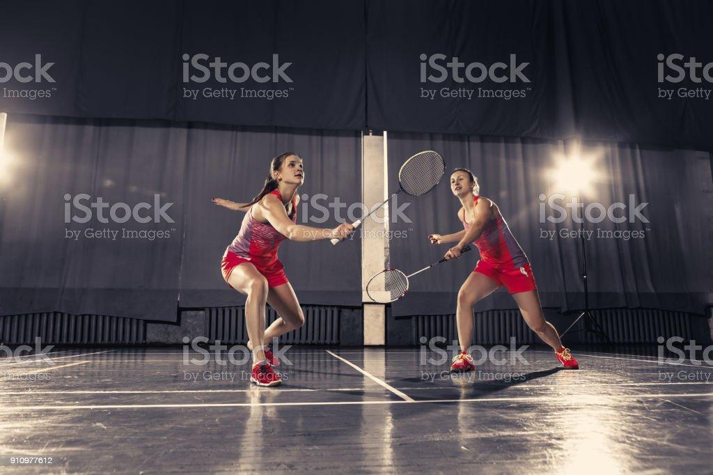 若い女性の体育館でバドミントン ストックフォト